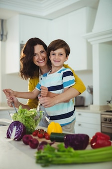 Portrait of mother and son mixing the salad in kitchen
