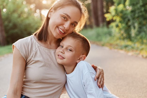 Portrait of mother and son smiling and hugging each other and looking at camera, happy family outdoor, having fun together in summer park, childhood, motherhood.