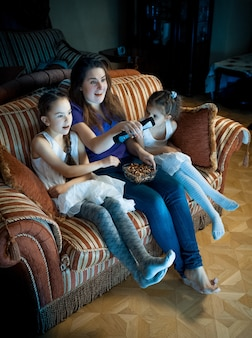 Portrait of mother and two daughters watching tv at night on sofa