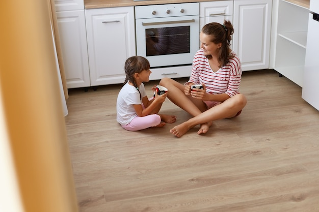 Portrait of mother with little daughter sitting on the floor in kitchen and drinking coffee or tea, little girl telling secrets to mommy, family being happy to spending time together.