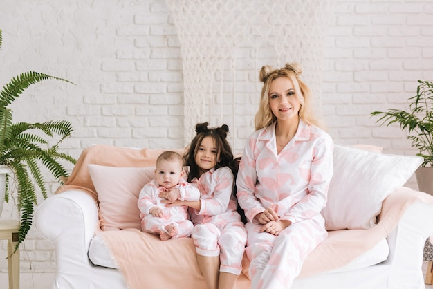Portrait of mother with two daughters in the white room in the same pink pajamas, family look