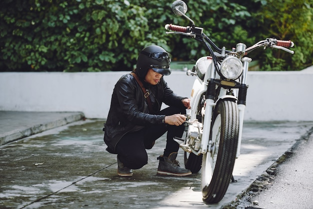 Portrait of motorcyclist preparing his vehicle for a ride