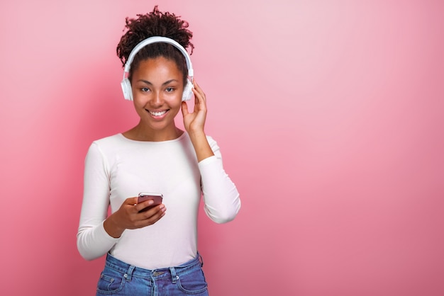 Portrait of a mulatto girl in earphones and holding a mobile phone looking at the camera