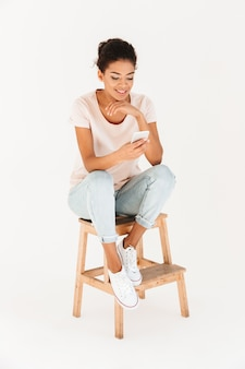 Portrait of mulatto woman in casual sitting on chair and holding mobile phone in hands, isolated over white wall