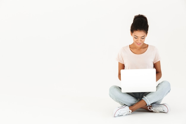 Portrait of mulatto woman in casual sitting on floor in lotus pose and holding laptop, isolated over white wall