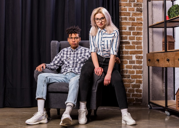 Portrait of multi ethnic couple sitting on armchair looking at camera