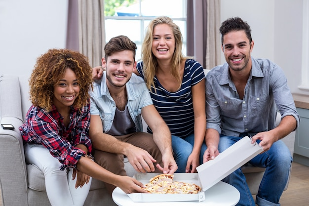 Portrait of multi ethnic friends enjoying pizza at home