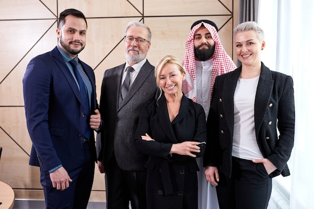 Portrait of multi-ethnic group of executives gathered at meeting to discuss ideas and strategies, diverse people in formal wear stand looking at camera, posing and smiling
