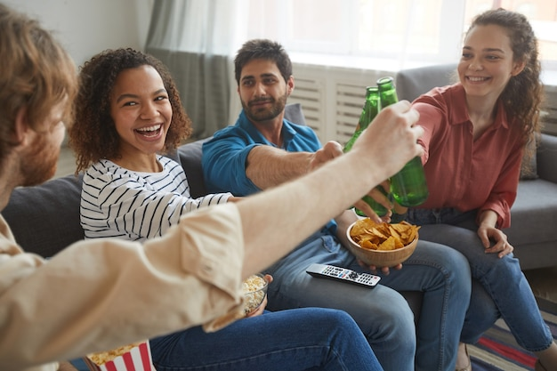 Portrait of multi-ethnic group of friends clinking beer bottles while watching tv together sitting on comfortable sofa at home