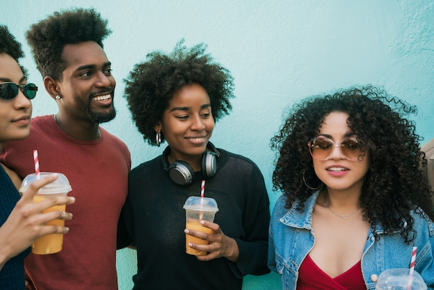 Portrait of multi-ethnic group of friends having fun together and enjoying good time while drinking fresh fruit juice.