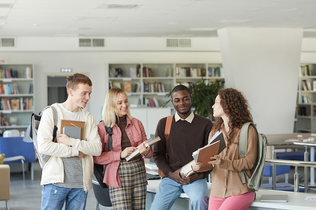 Portrait of multi-ethnic group of students standing in college library and chatting while holding books and backpacks,  above