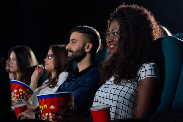 Portrait of a multicultural group of friends enjoying movies together at the cinema