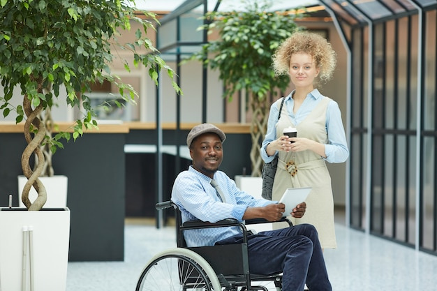 Portrait of multiethnic couple standing in the mall young woman standing near disabled african man