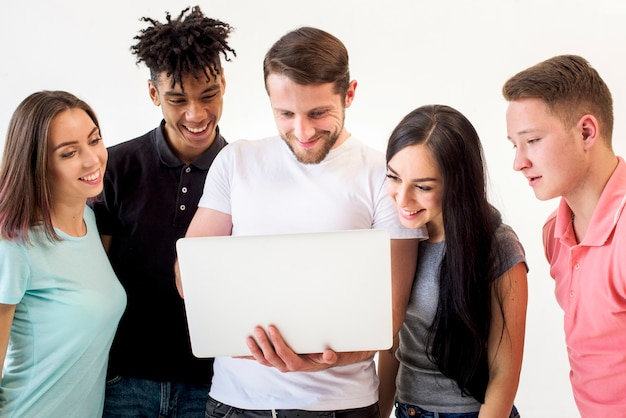 Portrait of multiethnic friends looking on laptop standing in white background