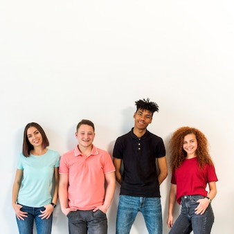 Portrait of a multiracial people standing against white wall