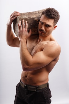 Portrait of a muscle, athlete, sexy, hot, fit brutal bearded man with haircut, with naked torso, holding a tree trunk on his shoulders, over white background.