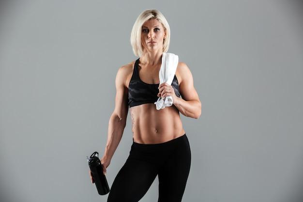 Portrait of a muscular adult sportswoman holding water bottle