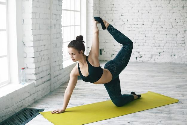 Ritratto di giovane donna dai capelli scuri in forma muscolare in abbigliamento sportivo elegante che pratica yoga nella grande palestra, in piedi nella posa della mucca sul tappeto verde, sollevando una gamba sopra la sua testa e tirandola con la mano