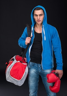 Portrait of a muscular guy with a sports bag.
