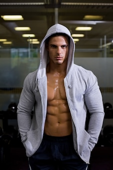 Portrait of a muscular man in hood jacket at gym