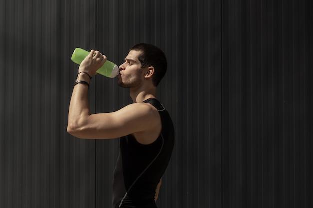 Портрет мускулистый мужчина берет перерыв, чтобы увлажнить его тело после