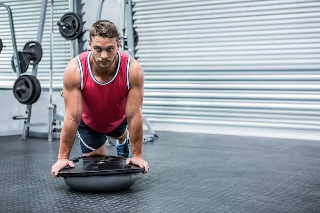 Portrait of muscular man using bosu ball
