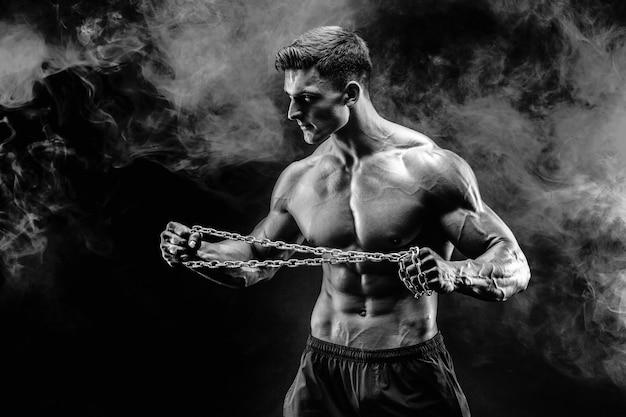 Portrait of muscular sportsman tearing metal chain