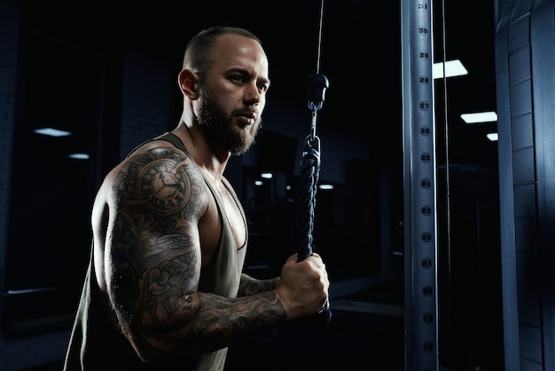 Portrait of muscular tattooed bodybuilder doing crossover exercise.