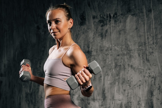 Portrait of muscular young athletic woman doing exercise with lifting weights and looking away.