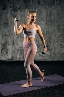 Portrait of muscular young athletic woman with perfect beautiful body wearing sportswear doing exercise with lifting weights and lunging forward. caucasian fitness female posing in studio.