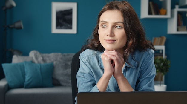 Portrait of musing young woman with her head rested on fists sitting in front of computer at home