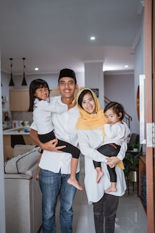 Portrait of muslim family standing in front of their front door house welcoming guest at home during eid mubarak celebration