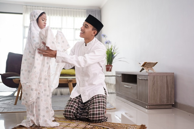 Portrait of muslim father teaching her daughter how to pray at home