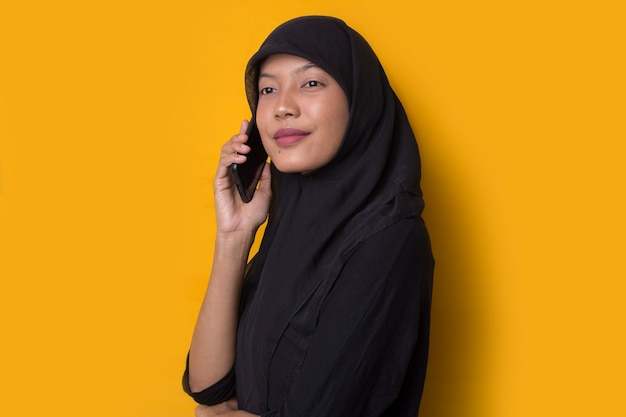 Portrait of muslim girl using a smartphone on yellow background
