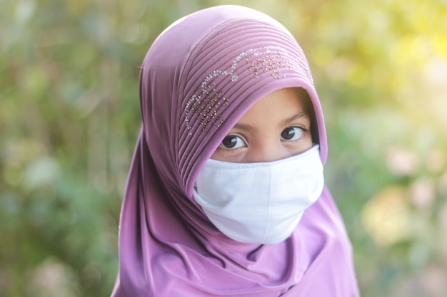 Portrait of muslim kid girl with hijab wearing mask. covid-19 or coronavirus concept.