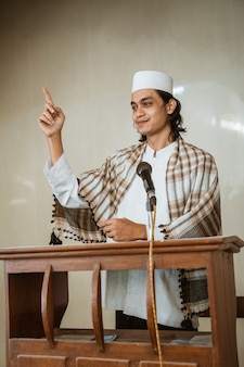 Portrait of muslim male preacher sharing about islam during prayer time in the mosque