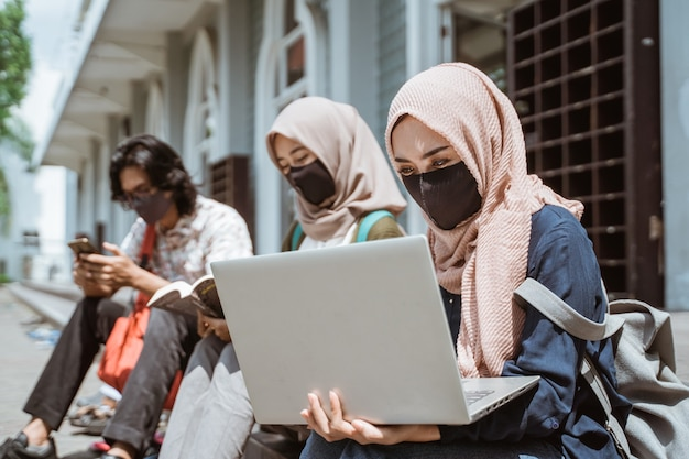 Portrait of muslim wearing masks female students who are busy doing their assignments on a laptop