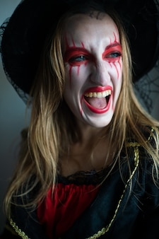 Portrait of a mysterious girl with fair hair as a witch with bright make-up and leaking lipstick mysteriously looks to the side with wide smile.