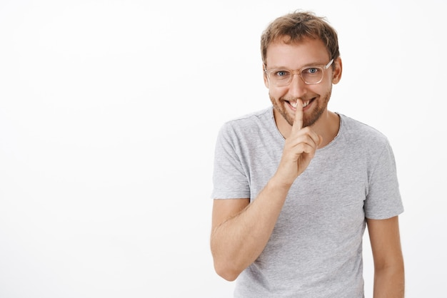 Portrait of mysterious handsome man with bristle in glasses and gray t-shirt smiling with enthusiasm saying shh, showing shush gesture with index finger over mouth