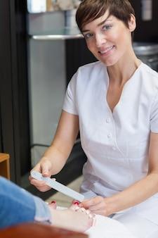 Portrait of nail technician filing womans toe nails