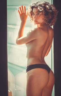 Portrait of a naked blonde woman posing  on the window