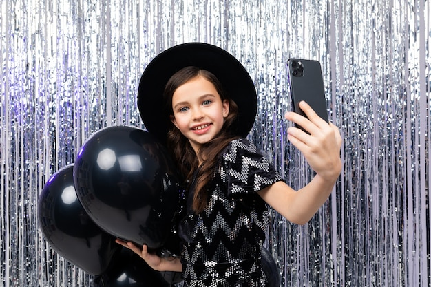 Portrait of a narcissistic teenager on a birthday taking selfie on a smartphone among black helium balloons on a shiny background