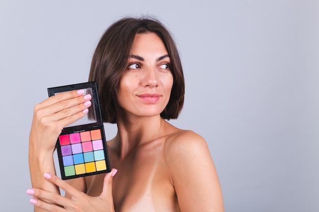 Il ritratto della donna di bellezza naturale tiene la tavolozza di colori di primavera estate luminosa degli ombretti sulla parete grigia
