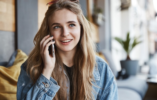 Portrait of natural girl sitting in cafe outdoors and talking on