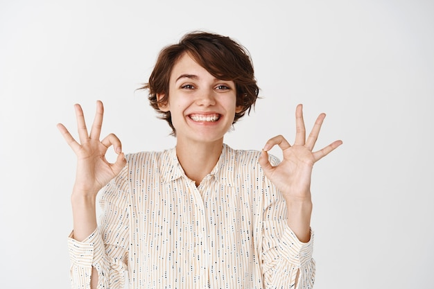 Portrait of natural happy woman with short hairstyle, showing okay gestures and smiling, approve and like something, show positive feedback, white wall