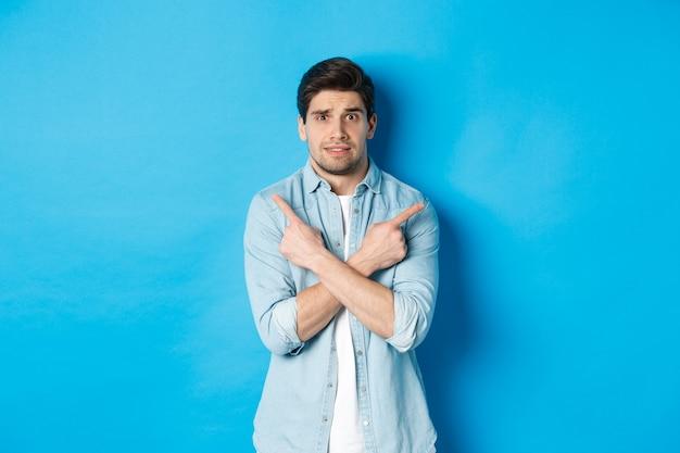 Ritratto di ragazzo nervoso che punta le dita lateralmente, sembra indeciso e chiede aiuto per la scelta, mostra offerte promozionali destra e sinistra, in piedi su sfondo blu