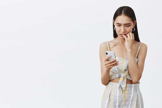 Portrait of nervous intense attractive and elegant female in cute outfit, biting fingernails while staring at smartphone screen anxiously