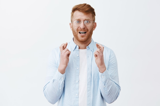 Portrait of nervous and intense masculine redhead male with bristle in transparent glasses, crossing fingers and frowning while anxiously hoping for something happen