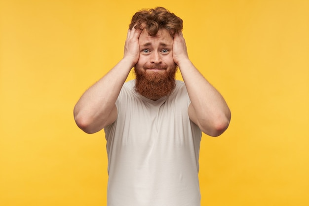 Portrait of nervous sad man with red hair and beard, wears blank t-shit, holds his head with both hands