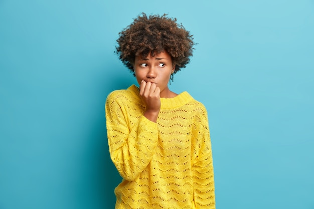 Portrait of nervous woman keeps hands near mouth feels concerned before important interview hesitates about something dressed in knitted yellow jumper poses against blue studio wall